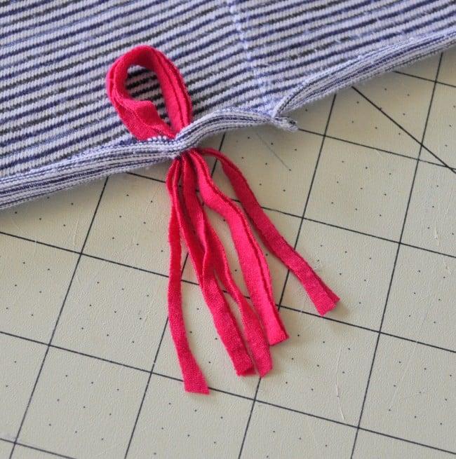 Pull tassel through slit in t shirt