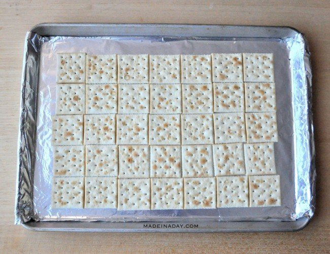 Line up saltines in a baking sheet