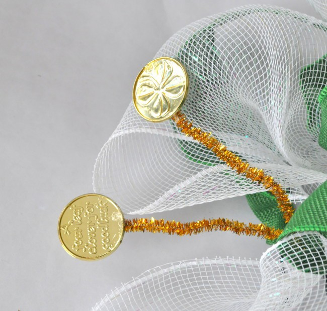 hot glue coins to pipe cleaners on mesh wreath