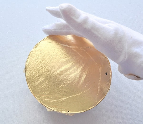 Gently press gold gilding sheets to items with cotton gloves