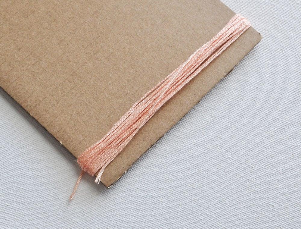embroidery thread on cardboard
