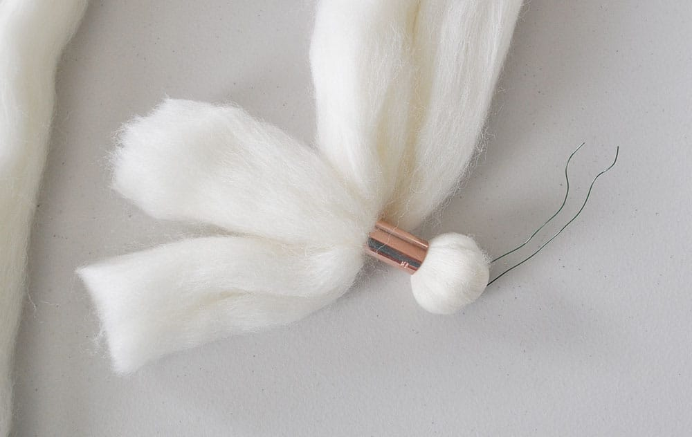Add a copper bead to wool roving wall hanging